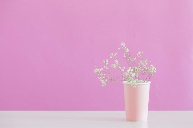 ピンクの背景の上に花瓶にカスミソウの花