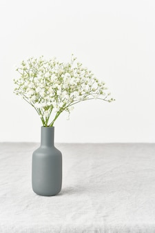 カスミソウの花の花瓶。柔らかな光、スカンジナビアのミニマリズム、白い壁