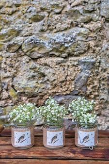 Цветы гипсофилы, стоящие в старинных стеклянных банках на камне