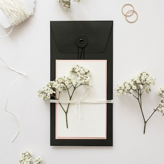 Gypsophila and greeting card tied with strings on white backdrop