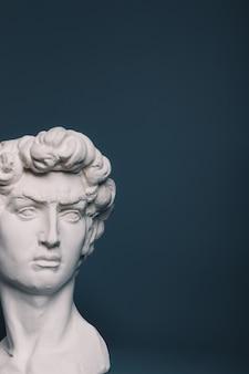 灰色の背景に彫刻ダビデ像の石膏コピー