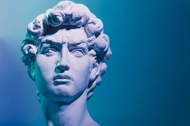 Gypsum copy of the sculpture david michelangelo on blue background