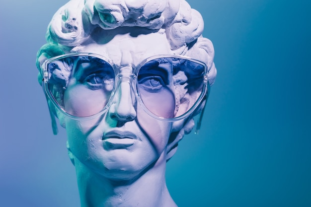 Gypsum copy of the sculpture david michelangelo in sunglasses on blue background