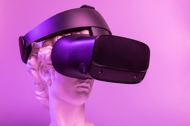 Gypsum copy of the sculpture david michelangelo in a virtual reality helmet on a pink background