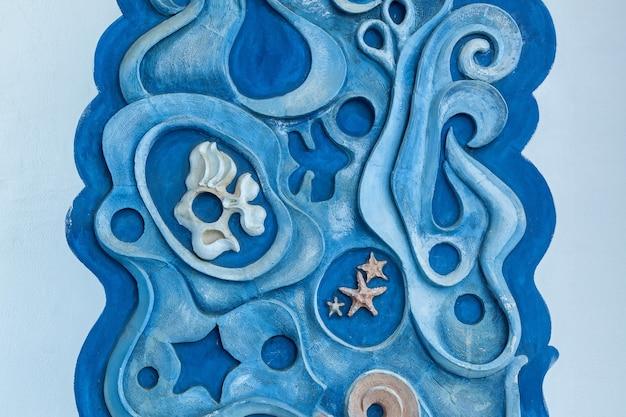 Гипсовый декоративный орнамент синего цвета с морскими обитателями на белой стене. море и рыбы на стене