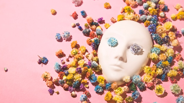Gypsum face of a girl in flowers. spring creative concept.