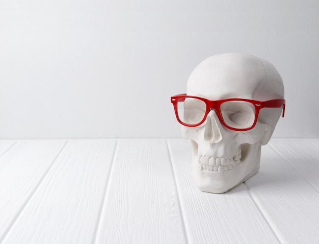 흰색 나무 테이블에 빨간 안경에 석고 인간의 두개골