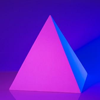 Гипсовая пирамида в розовом и голубом неоновом свете