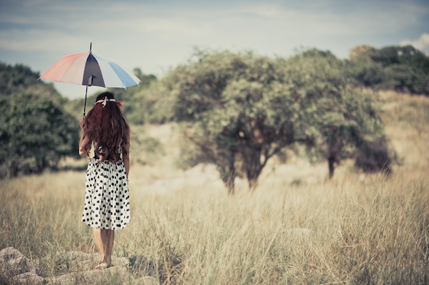 A gypsy girl holding umbrella and stand alone in the grassland