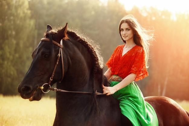 Цыганка катается на лошади в поле летом. женщина с длинными волосами гладит и ласкает лошадь, стоящую в зеленой траве