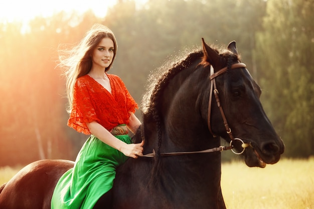 Gypsy girl rides a horse in a field in the summer.