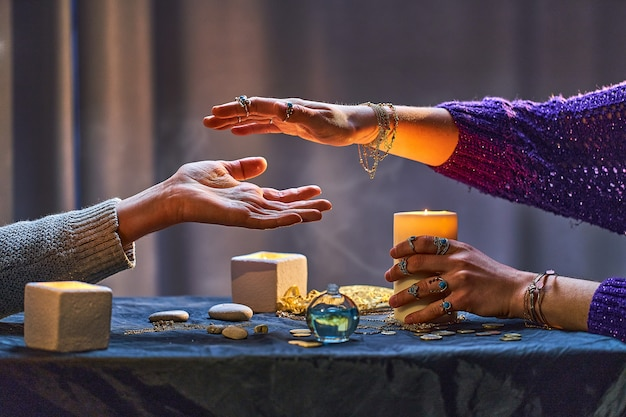 Gypsy witch woman during palmistry and divination ritual around candles and other magical accessories. magic illustration