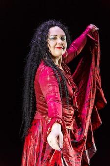 長い黒髪の裸足のジプシーの女性は、黒い背景に赤いドレスを着て踊ります。縦の写真