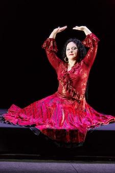 長い黒髪の裸足のジプシーの女性は、黒い背景に赤いドレスを着て両手で動きを踊ります。縦の写真