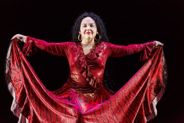 長い黒髪のジプシーの女性は、黒い背景に赤いドレスを着て踊ります。横の写真