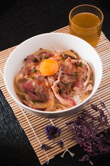 Гюдонская говядина с рисом. яйцо и лук крупным планом в миске. японская кухня
