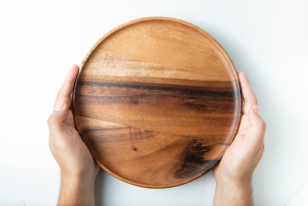 H holding empty wooden plate isolated on white, top view.