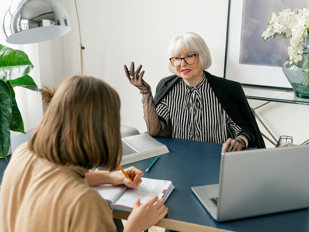H lady boss in striped blouse gloves and jacket in office giving tasks to her assistant