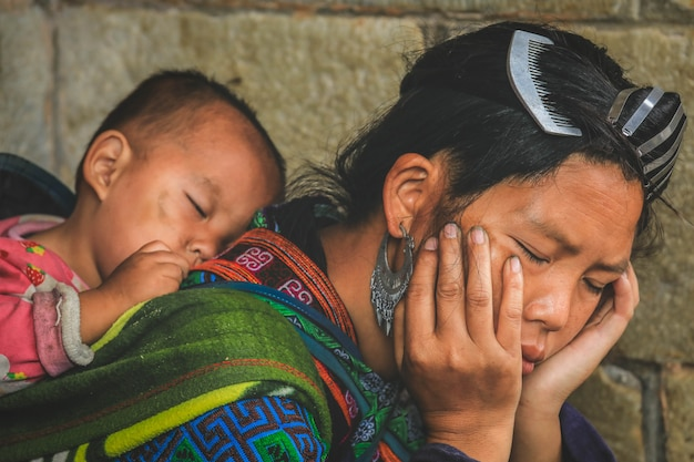 若い母親のh'mongが昼寝をして、ベトナムのサパで赤ちゃんを背負っています。