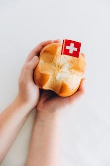 ドイツ語で呼ばれるhの伝統的なパンaugustweggen十字形のパンパンを持っている子供の手