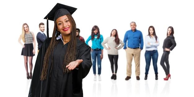 誰かを迎えるために手を差し伸べるまたはhに身振りで示すお下げを着て若い卒業黒人女性