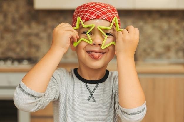家で楽しんでいる面白い少年は、hの前にクッキーフォームの星を保持しています。