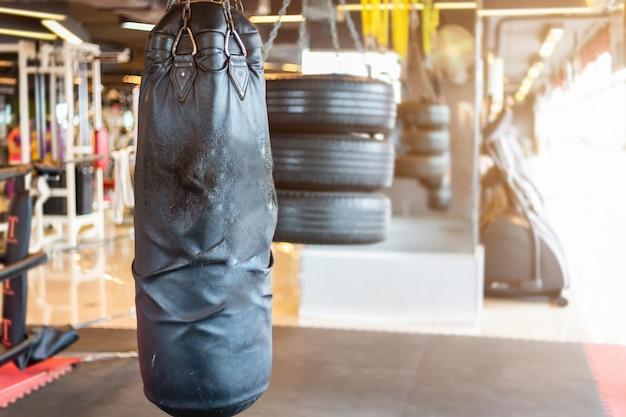 多重ボクシングジムのインテリアとフィットネスhの抽象的なぼかしにぶら下がっている黒いパンチングバッグ