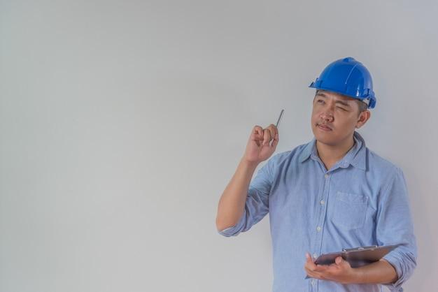 思いやりのある若い男の建築家またはインテリアデザイナー、彼はペンとクリップボードをhで保持しています