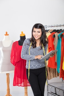 Молодая азиатская дизайнерская женщина используя таблетку и усмехающся, одежда ha