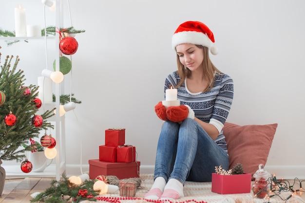Счастливая девушка с рождественскими подарками в помещении