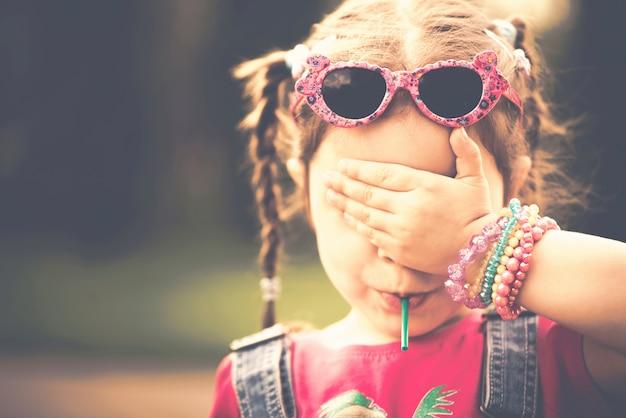 Haappy маленькая девочка с конфетой на открытом воздухе в парке
