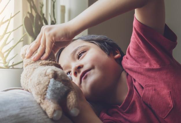 Голова жизнерадостного ребенк лежа вниз на софе играя с игрушкой собаки, мальчик ребенка с haapy лицом играя с его мягкой игрушкой или отдыхая дома.