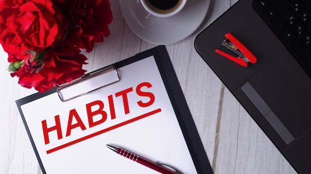 Habits는 노트북, 커피, 빨간 장미, 펜 근처의 흰색 메모장에 빨간색으로 적혀 있습니다.