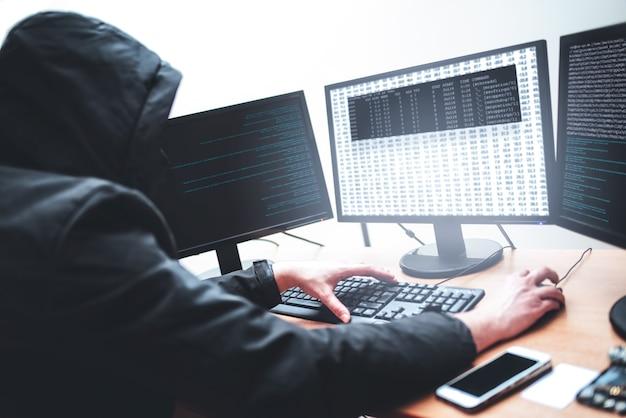 Концепция взлома. изображение мужчины-хакера, пытающегося украсть информацию из системы, глядя на компьютер, изолированное на белом фоне