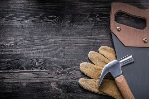 Hack-saw claw hammer protective leather gloves on wood board