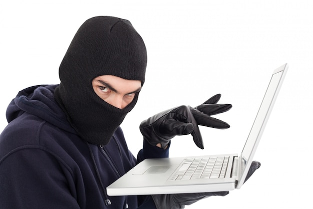 Hacker in balaclava standing and typing on laptop on white background