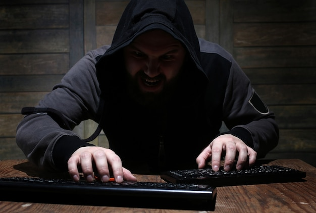 Hacker in the black hood in a room with wooden walls