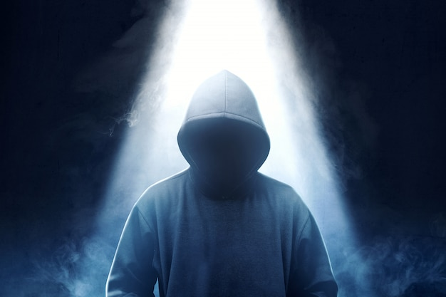 Hacker in black hoodie standing with smoke and light from the top