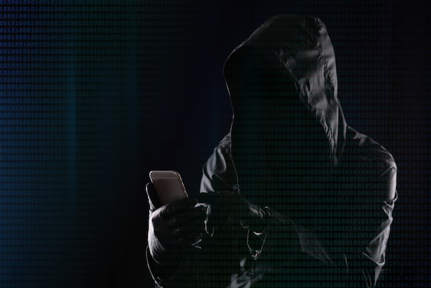 Hacker in a dark hood hacks into a modern mobile phone on the background of binary code, internet personal data security concept.