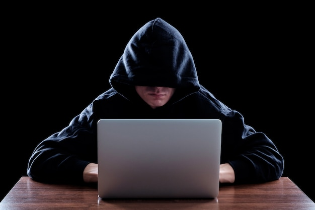 Hacker in a dark hoody sitting in front of a notebook