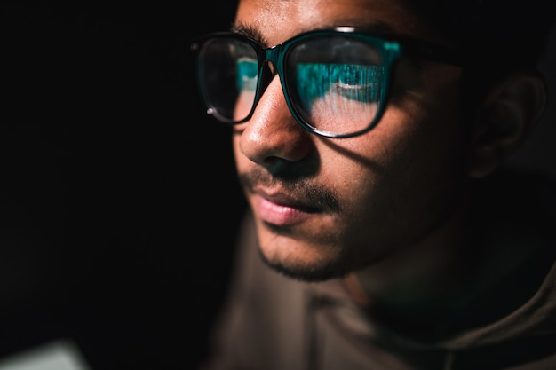 Hacker in glasses and a hood works at a computer in the dark, a reflection in glasses