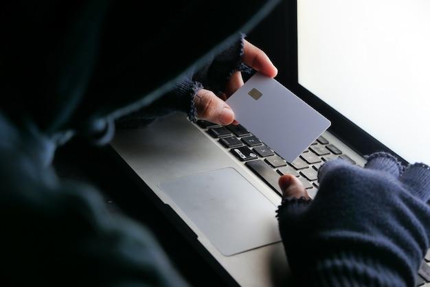 신용 카드에서 데이터를 훔치는 해커 손.