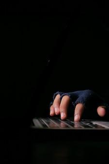 Хакер вручную крадет данные с ноутбука сверху вниз.