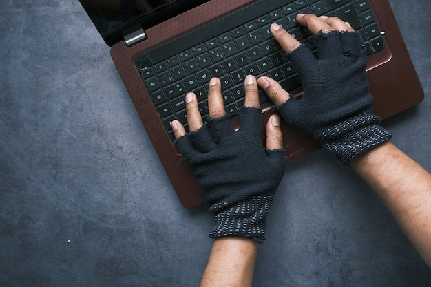 Hacker hand stealing data from laptop top down