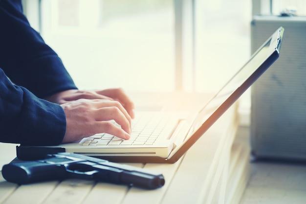 Hacker holding gun working on his computer