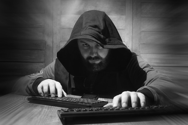 The hacker in the hood sits and works behind the computer