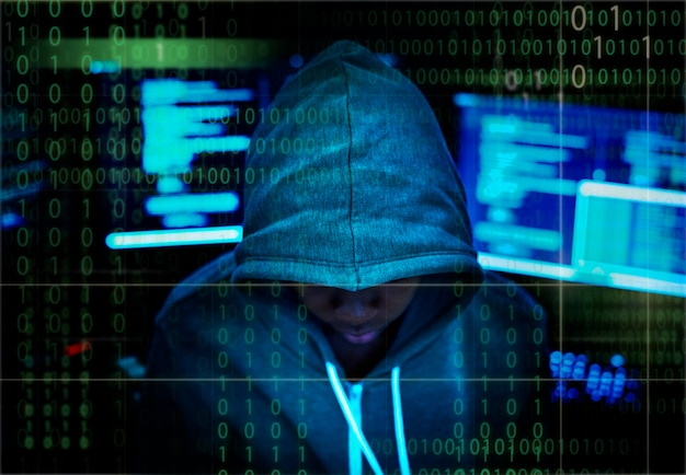 Hacker in a hoody with computer background