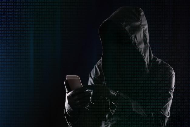 Хакер в темном капюшоне взламывает современный мобильный телефон на фоне двоичного кода, концепции безопасности личных данных в интернете.