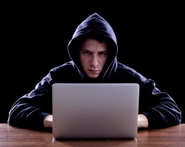 ノートブックの前に座っている暗いフーディーのハッカー