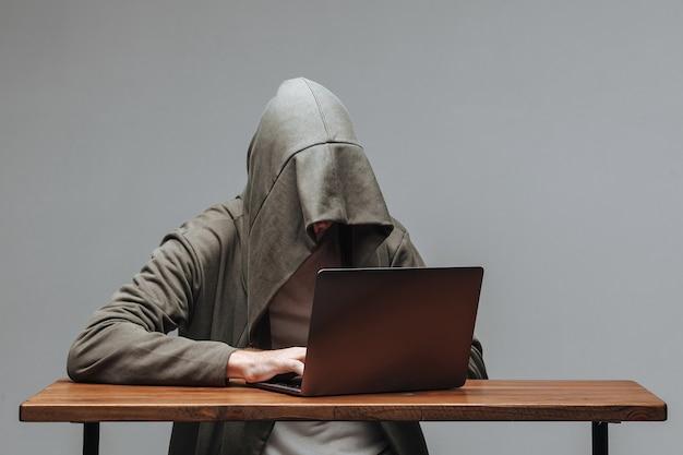 Хакер в капюшоне без лица сидит за ноутбуком